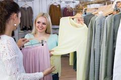 Excited молодые женщины выбирая пуловер и юбку стоковая фотография