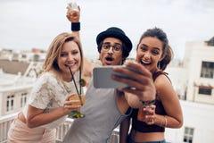 Excited молодые люди принимая автопортрет в партии Стоковое Фото