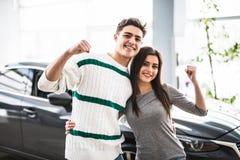 Excited пары покупая автомобиль на торговце с оружием вверх стоковое изображение