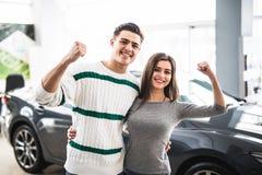 Excited пары покупая автомобиль на торговце с оружием вверх Стоковые Изображения