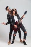 Excited пары рок-н-ролл играя электрическую гитару Стоковое Изображение
