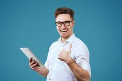 Excited рубашка и стекла молодого человека нося белая используя ПК таблетки давая большие пальцы руки вверх показывать стоковые изображения