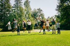 Excited семья 11 скача в парк лета Стоковая Фотография
