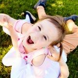Excited сторона маленькой девочки сидя на ее брате Стоковая Фотография