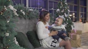 Excited счастливая мать молодой женщины играя с ее младенцем мальчика в рождественской елке украсила праздничную уютную комнату с видеоматериал