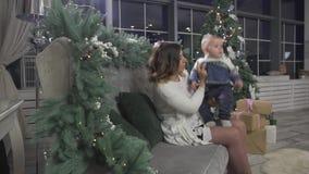 Excited счастливая мать молодой женщины играя с ее ребёнком в рождественской елке украсила праздничную уютную комнату студии сток-видео