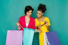 Excited счастливые многонациональные девушки с хозяйственными сумками Стоковое фото RF