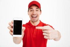 Excited счастливый молодой дисплей показа работника доставляющего покупки на дом мобильного телефона Стоковая Фотография RF