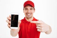 Excited счастливый молодой дисплей показа работника доставляющего покупки на дом мобильного телефона Стоковые Фото