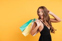 Excited удивленная молодая дама держа хозяйственные сумки Стоковая Фотография