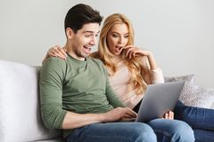 Excited удивленные молодые любящие пары используя портативный компьютер Стоковое Изображение