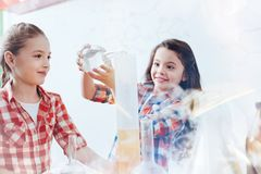Excited умные девушки смешивая жидкости во время урока химии на школе Стоковые Фото