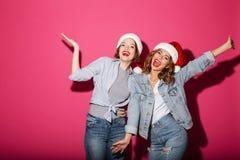 Excited усмехаться 2 друз женщин нося шляпы santa рождества Стоковые Фото