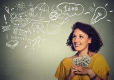 Excited успешная молодая бизнес-леди держа долларовые банкноты денег в руке Стоковая Фотография