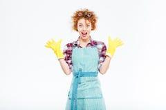 Excited удивленная домохозяйка в голубой рисберме и желтых резиновых перчатках Стоковые Изображения RF