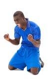Excited футболист в голубой веселить на его коленях стоковые изображения