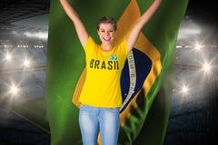 Excited футбольный болельщик в футболке Бразилии держа флаг Бразилии Стоковая Фотография