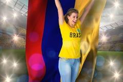 Excited футбольный болельщик в футболке Бразилии держа флаг Колумбии Стоковые Фотографии RF
