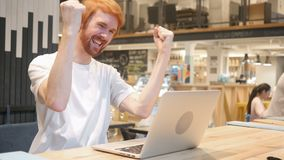 Excited человек бороды Redhead празднуя успех, сидя в кафе акции видеоматериалы