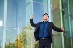 Excited человек поднимая его оружия стоковая фотография