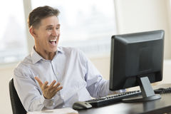 Белизна excited бизнесмена крича используя настольный ПК Стоковая Фотография