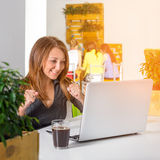 Excited счастливая коммерсантка при поднятые оружия сидя на таблице с компьтер-книжкой празднуя ее успех Зеленая концепция офиса  Стоковая Фотография