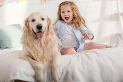 Free Excited Adorable Kid And Golden Retriever Sticking Tongues Out Together On Bed Stock Photos - 154830703
