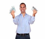 Excited adult man holding cash money. Portrait of an excited adult man looking at you and holding cash money against white background Royalty Free Stock Photo