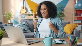 Excited African American business lady enjoying success at freelance work at home