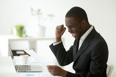 Excited african american businessman reading letter with unexpec. Excited african-american businessman holding letter with unexpected good news, happy black royalty free stock photography