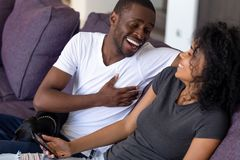 Excited African American couple laughing at funny joke together stock photo