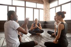 Excited african-american man talking to diverse friends sitting. Excited african american men talking to sporty happy diverse friends sitting on mat in studio Stock Photography