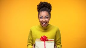 Excited African-American woman holding gift box, pleasant birthday surprise stock images