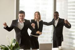 Excited african and caucasian employees dancing in office, celeb Stock Images