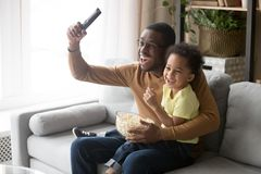 Excited african father with son watching football game on tv royalty free stock photos