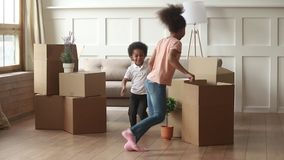 Excited african kids running playing with boxes on moving day