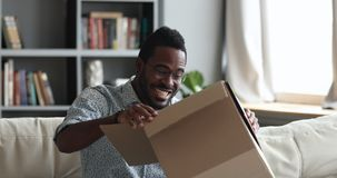 Excited african male customer receiving opening parcel box at home