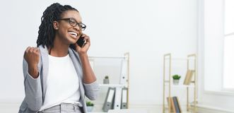 Excited African Woman Talking On Phone Celebrating Success stock photography