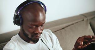 Enjoying the Music. Excited afro-american man wears headphones enjoying music sitting on grey sofa, indoors close up shot stock footage
