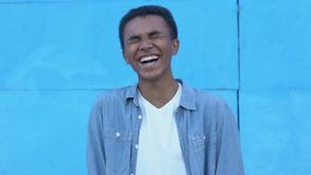Excited afro-american teen boy laughing on blue background, sincere happiness