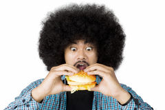 Excited Afro man eating a burger. Closeup of an Afro man looks excited while eating a burger, isolated on white background Stock Images