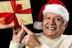 Excited Aged Man Pointing At Golden Gift In Hand. Enthusiastic male senior is pointing his left index finger at a golden wrapped gift held at eye-level in his Royalty Free Stock Image