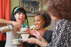 Excited Alcoholics Indulging in Booze. Mixed group of three excited women drinking booze in teacups Stock Photography