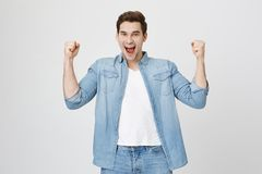 Excited and amazed young european man raising fists, expressing happiness and victory. Football player cheers for his royalty free stock photography