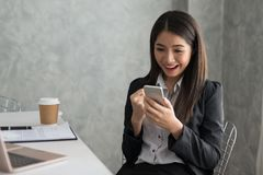 Excited asian business girl while reading a smart phone sitting. In her workstation. Business Success Concept Royalty Free Stock Images