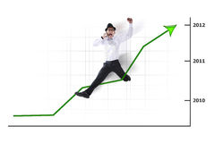 Excited Asian businessman jumping with chart Royalty Free Stock Photography