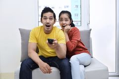 Excited asian couple sitting on the couch and watching movies Stock Image