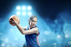 Excited asian girl basketball player defending the ball from opponent on the basketball court stock photo