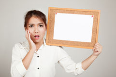 Excited Asian girl with blank paper pin on cork board. On gray background Royalty Free Stock Photography