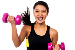 Excited asian girl lifting dumbbells Stock Photography